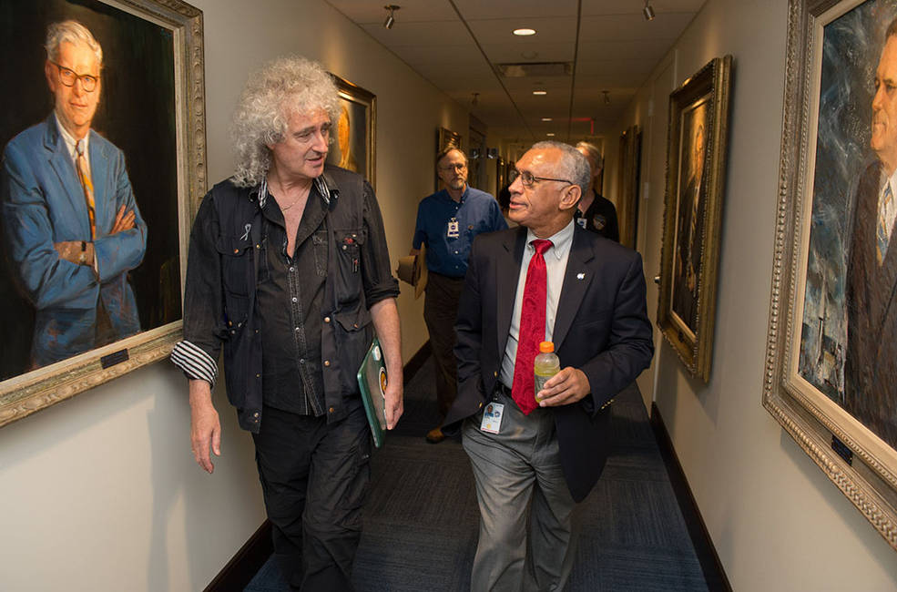 """Queen lead guitarist and astrophysicist Dr. Brian May and NASA Administrator Charlie Bolden discuss the New Horizons mission prior to a science briefing on July 17, 2015 in Washington, D.C. Dr. May described the long weekend with the New Horizons team as """"the best birthday gift ever."""" Image Credit: NASA/Joel Kowsky"""