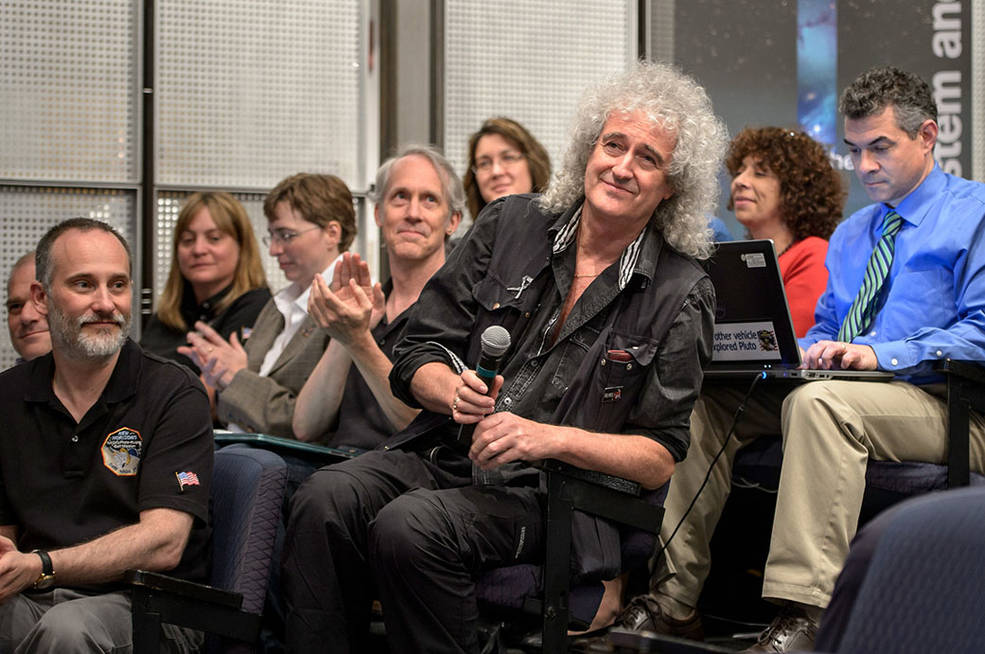 Astrophysicist Dr. Brian May is recognized during a July 17, 2015 New Horizons science briefing at NASA Headquarters, Washington, D.C. May spent a long birthday weekend with the science team, attending two morning science plenaries, a meeting with the Student Dust Counter group, and working on stereo images of Pluto with the Geology, Geophysics and Imaging (GGI) team. Image Credit: NASA/Joel Kowsky
