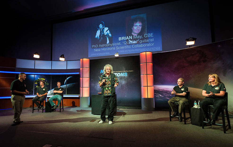 """Dr. Brian May addresses a crowd of mostly kids and their families during a July 18, 2015 """"Plutopalooza"""" event at Johns Hopkins Applied Physics Laboratory, Laurel, Maryland, as members of the New Horizons team look on. Left to right: Mike Buckley, Jamey Szalay, Hal Weaver, Alan Stern, Cathy Olkin. Image Credit: JHUAPL/Edward Whitman"""