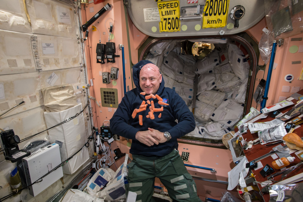 Expedition 43 astronaut Scott Kelly is photographed with carrots floating around him in the Node 1 module. A table covered in other food packets is beside him. Image Credit: NASA