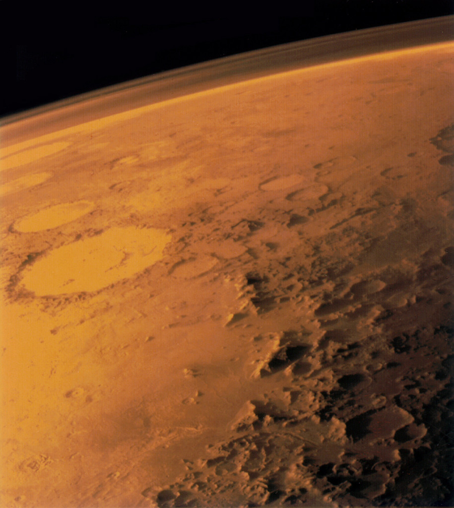 In this image taken by the Viking 1 orbiter in June 1976, the translucent layer above Mars' dusty red surface is its atmosphere. Compared to Earth's atmosphere, the thin Martian atmosphere is a less powerful shield against quick-moving, energetic particles that pelt in from all directions – which means astronauts on Mars will need protection from this harsh radiation environment. Image Credit: NASA/Viking 1