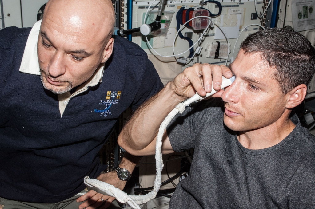NASA astronaut Michael Hopkins (at right), Expedition 37 flight engineer, performs ultrasound eye imaging in the Columbus laboratory of the International Space Station. European Space Agency astronaut Luca Parmitano, flight engineer, assists. Image Credit: NASA