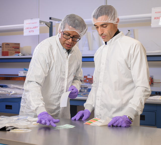 Using adhesive tape as a sampling device, Venkateswaran and Karouia demonstrate one of the methods that station crew used to collect microorganisms from surfaces for the Microbial Tracking-1 investigation. Image Credit: NASA/Dominic Hart