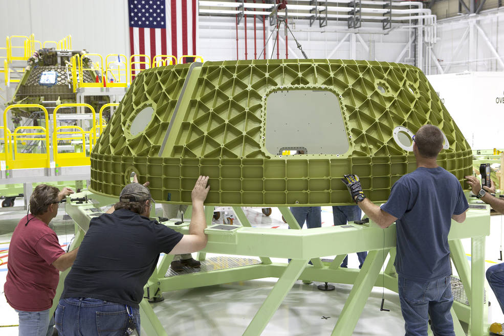 Technicians lower the upper dome of a Boeing Starliner spacecraft onto a work stand inside the company's Commercial Crew and Cargo Processing Facility at NASA's Kennedy Space Center in Florida. The upper dome is part of Spacecraft 1, a Starliner that will perform a pad abort flight test as part of the development process of the spacecraft in partnership with NASA's Commercial Crew Program. In the background is the Starliner Structural Test Article. Image Credit:  NASA/Dimitri Gerondidakis