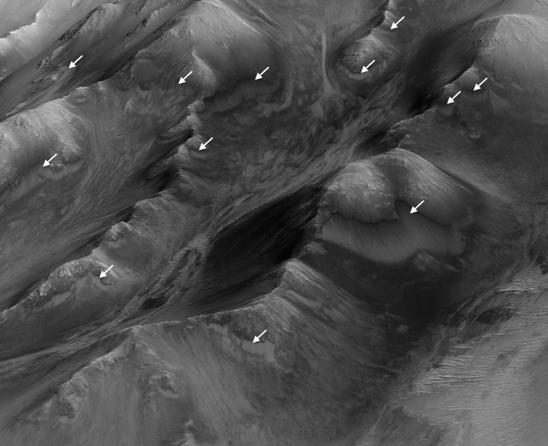 """The white arrows indicate locations in this scene where numerous seasonal dark streaks, called """"recurring slope lineae,"""" have been identified in the Coprates Montes area of Mars' Valles Marineris by repeated observations from orbit. Image Credit: NASA/JPL-Caltech/Univ. of Arizona"""