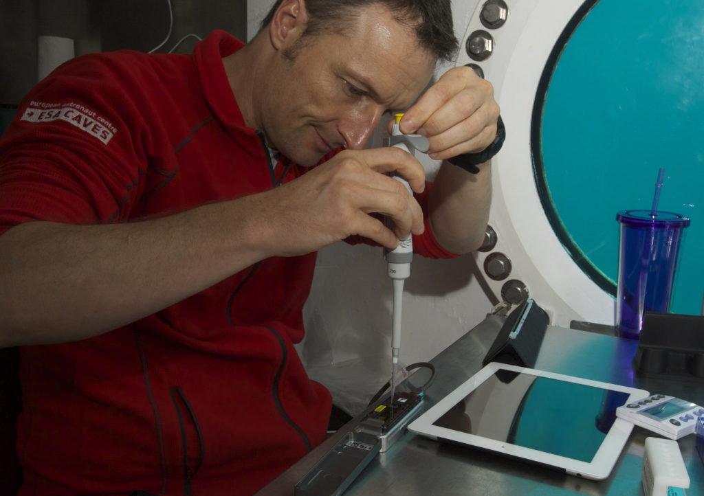 NASA Extreme Environment Mission Operations (NEEMO) crew member, Matthias Maurer of ESA, works on inserting samples into the MinION DNA sequencer as part of the Biomolecule Sequencer experiment. Researchers tested the device aboard the analog to minimize unknowns and see how the device worked in various extreme environments. Image Credit: NASA