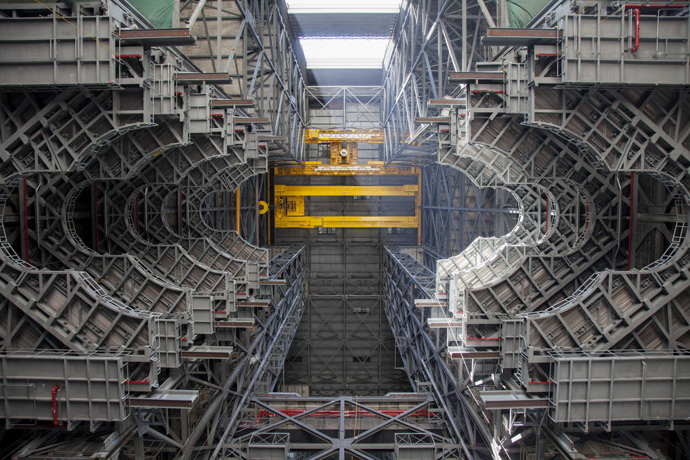 A heavy-lift crane lifts the first half of the F-level work platforms, F south, for NASA's Space Launch System rocket, into position for installation July 15, in High Bay 3 of the Vehicle Assembly Building at NASA's Kennedy Space Center in Florida. Image Credit: NASA/Bill White