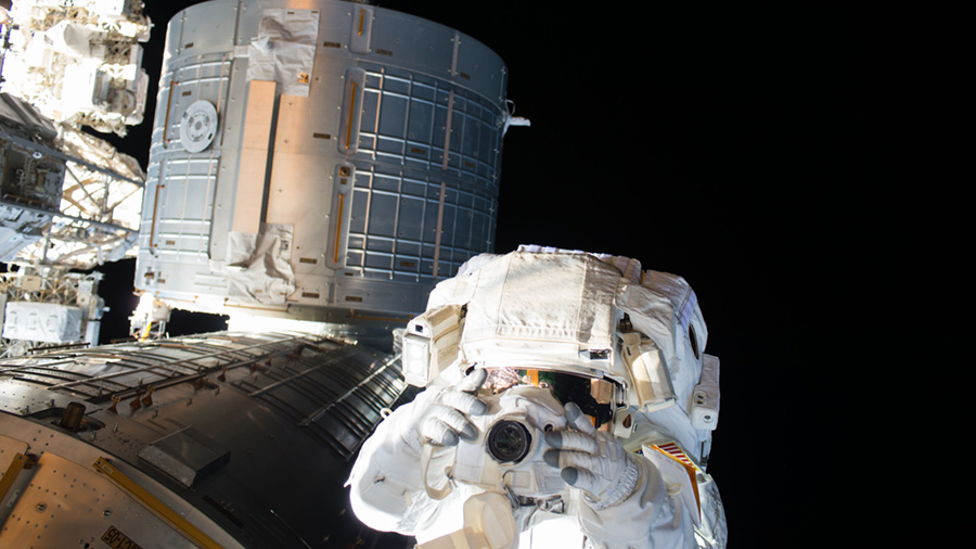 Astronaut Kate Rubins is seen taking taking photographs with the Japanese Kibo lab module behind her during a spacewalk on Aug. 19. Image Credit: NASA TV