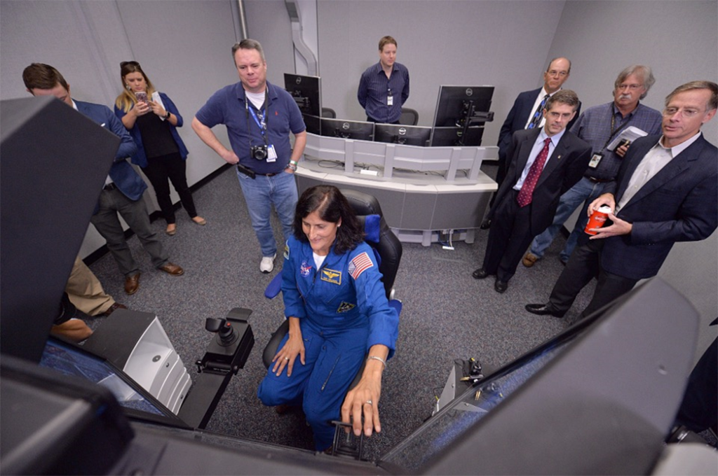 NASA Commercial Crew Program astronaut Sunita Williams demonstrates Boeing's Crew Part-Task Trainer, which is being used to prepare crew members to fly to the International Space Station aboard Boeing's CST-100 Starliner Spacecraft. Image Credit: NASA/Lauren Harnett