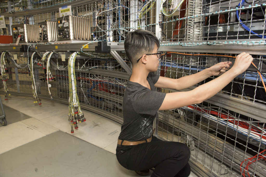 Ratana Meekham, a Qualis Corp. engineering technician at NASA's Marshall Space Flight Center, helps install approximately 5 miles of cable on a half-ring structure being used to test the avionics system that will guide the SLS. The forward skirt, intertank and engine section contain the rocket's avionics and electronics. Image Credit: NASA/MSFC/Fred Deaton