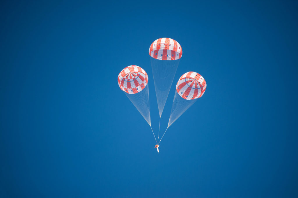 An Orion test article descends under three main parachutes during the first evaluation to qualify the spacecraft's parachute system for flights with astronauts. Image Credit: NASA