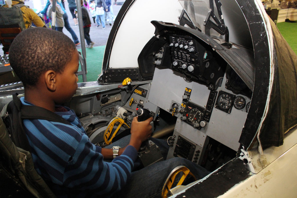 """Jayden Carothers, 11, takes the """"controls"""" of a simulated high performance jet cockpit. Image Credit: NASA/Jay Levine"""